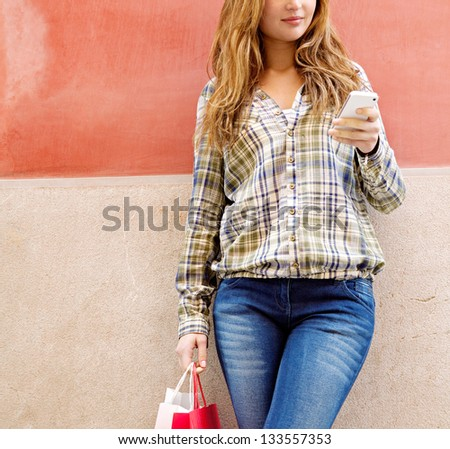 Attractive young woman leaning on a colorful orange city wall using a high tech smartphone and carrying shopping bags, smiling.