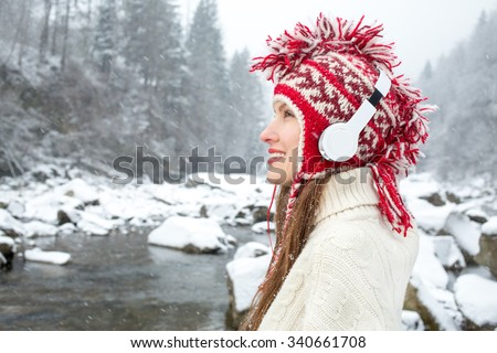 Attractive young woman listening to music on the music player in winter scenery - stock photo