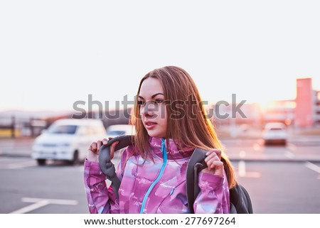 Attractive young woman looking aside while handing her backpack. A bit tired but still ready to continue her trip. Freedom, tourism and backpacking concept. Urban scenery - stock photo