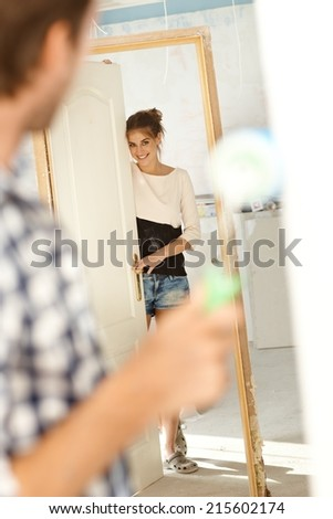Attractive young woman looking at man in new house under construction. Woman looking through door frame, man painting wall. - stock photo