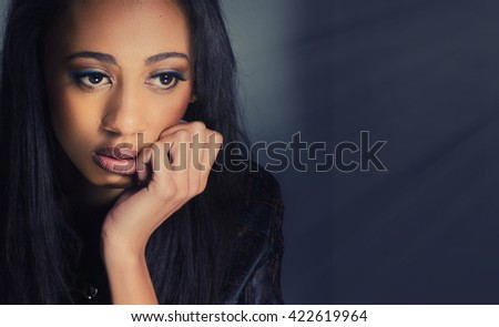 Attractive young woman looking thoughtful and contemplative.