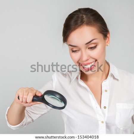 Attractive young woman looking through a magnifying glass - stock photo