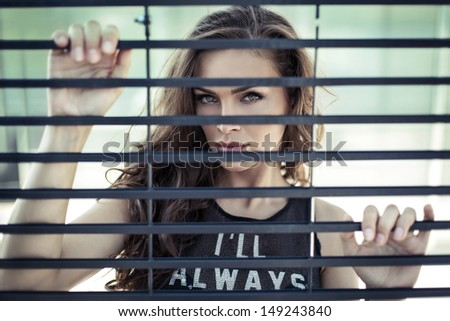 Attractive young woman looking through at the grate  - stock photo
