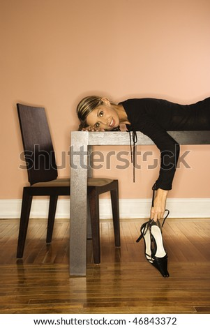 Attractive young woman lying on a table holding her shoes and smiling. Vertical shot - stock photo