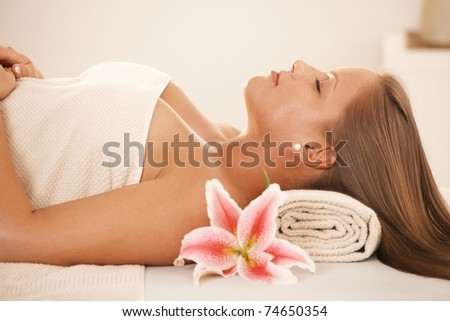 Attractive young woman lying on massage bed at spa, sleeping.? - stock photo