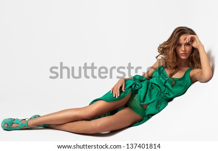 Attractive young woman lying on white background in fashion dress - stock photo