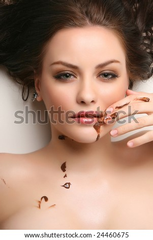 attractive young woman lying on white background with chocolate smeared - stock photo