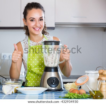Attractive young woman making croquettes using blender at home