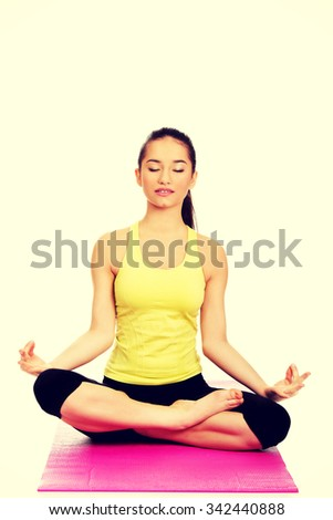 Attractive young woman meditating in pose of lotus. - stock photo