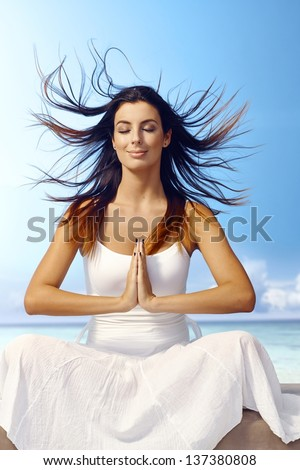 Attractive young woman meditating on the beach eyes closed, wind blowing hair, smiling, sitting in prayer position. - stock photo