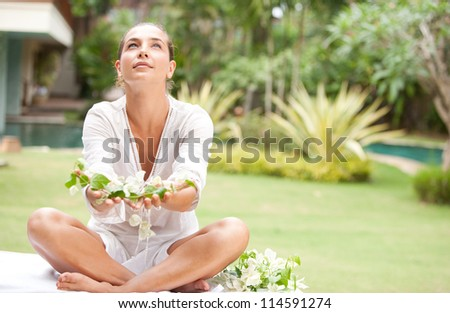 Attractive young woman offering and holding tropical flowers in her hands, in an exotic spa garden. - stock photo