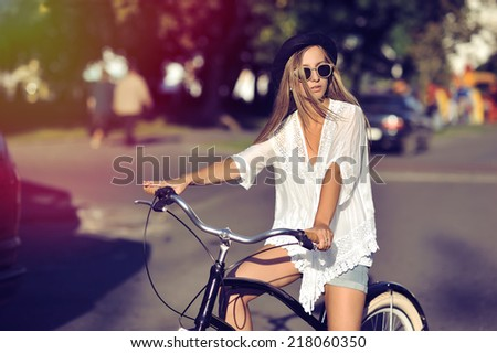 Attractive young woman on a bicycle in a city - stock photo