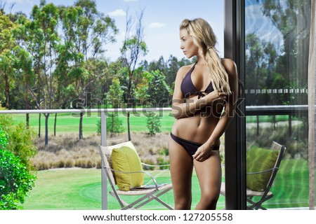 Attractive young woman on balcony overlooking a golf course - stock photo