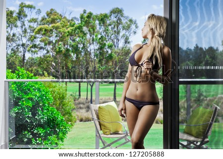 Attractive young woman on balcony overlooking a golf course