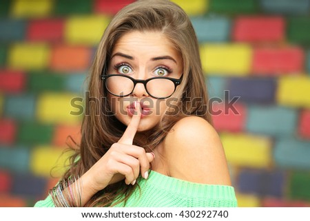 Attractive young woman on blurred brick wall background - stock photo