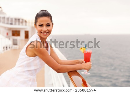 attractive young woman on cruise having cocktail - stock photo