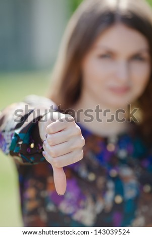 Attractive young woman on open air. Cute girl showing thumb down. Focus on foreground