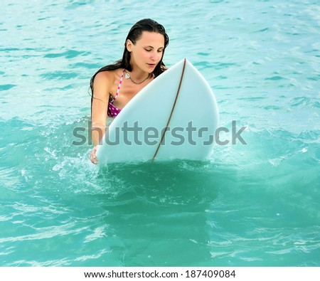 Attractive young woman on surfboard in the ocean drifting on the spot - stock photo