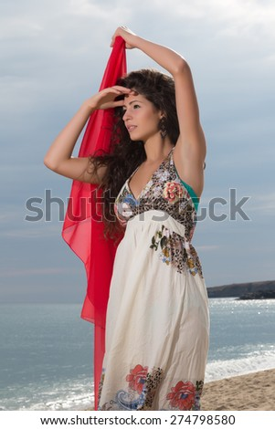 Attractive young woman on the beach waving with a red chiffon scarf  - stock photo