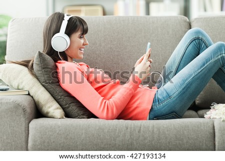 Attractive young woman on the sofa at home, she is playing music with her smarphone and wearing headphones, leisure and entertainment concept - stock photo