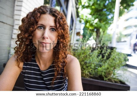 attractive young woman outside at cafe - stock photo