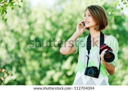 attractive young woman park talking phone two camera neck hand - stock photo