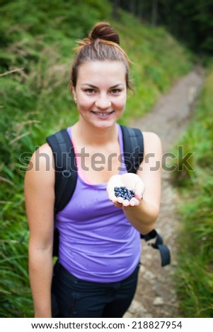 Attractive young woman picking and eating sweet, fresh, tasty blueberries (forest path in background, focused on palm full of blueberries) - stock photo