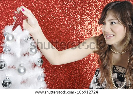 Attractive young woman placing a shooting star on top of a Christmas tree, in a red glitter background.