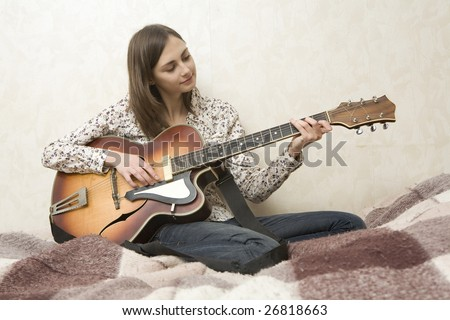 Attractive young woman playing guitar sitting on bed - stock photo