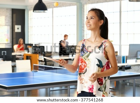 Attractive young woman playing table tennis in office.