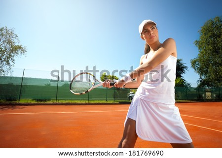 attractive young woman playing tennis - stock photo