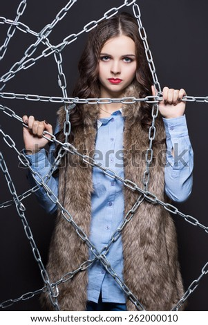 Attractive young woman posing behind the chains - stock photo