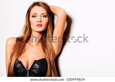 Attractive young woman posing by the wall. - stock photo