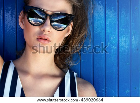 Attractive young woman posing in fashionable sunglasses. Sunny day. Summer style. Stripes.Portrait. - stock photo