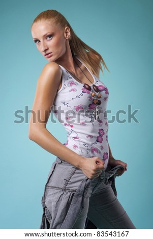 attractive young woman posing in studio on aqua background
