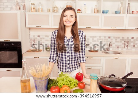 Attractive young woman posing in the kitchen and going to make dinner