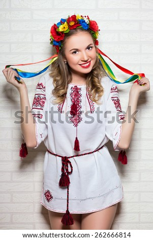 Attractive young woman posing in Ukrainian folk blouse and wreath - stock photo
