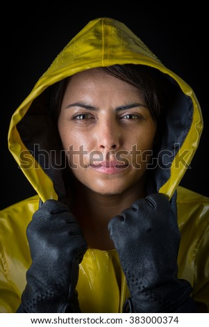 Attractive young woman posing with a yellow raincoat and black gloves - stock photo