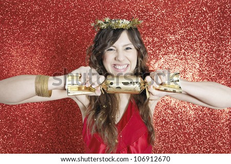 Attractive young woman pulling a Christmas cracker open while standing on a red glitter background. - stock photo
