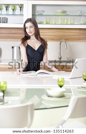 Attractive young woman reading a recipe book while enjoying a glass of wine in the kitchen