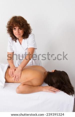 Attractive young woman receiving back massage at spa center - stock photo