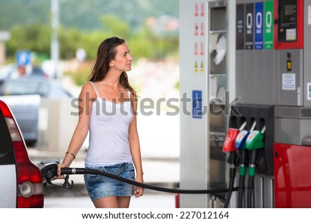 Attractive, young woman refueling her car in a gas station, checking the amount of gas, disliking the price tag and the gas mileage of her engine - stock photo