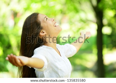 Attractive young woman rejoicing in a spring or summer garden standing sideways with her arms outstretched and her head raised to the heavens enjoying the freshness and beauty of nature - stock photo