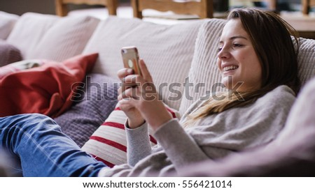 Attractive young woman relaxing at home on her couch using her cell phone