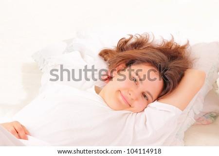Attractive young woman relaxing in bed - stock photo