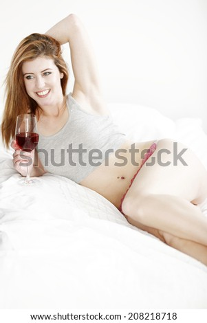 Attractive young woman relaxing on her bed at home.