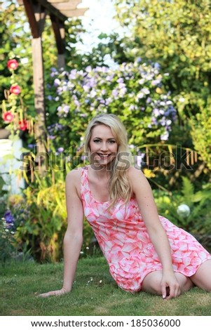 Attractive young woman relaxing on the grass in the shade of a tree in a summer garden smiling at the camera - stock photo