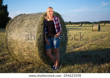 attractive young woman relaxing outdoors standing against hay roll - stock photo
