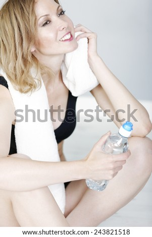 Attractive young woman relaxing with water bottle after fitness training - stock photo