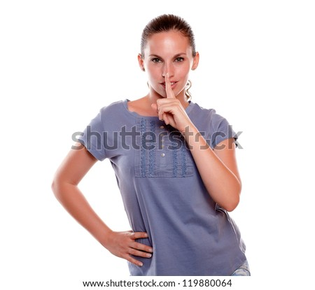 Attractive young woman requesting to you silence on blue shirt against white background - stock photo